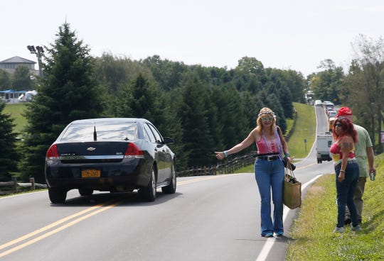 From left, Diane Wencke and Debra Bonner of Lincoln, Rhode Island attempt to hitchhike to the pavilion at Bethel Woods Center for the Arts for the 50th anniversary of Woodstock on August 15, 2019.