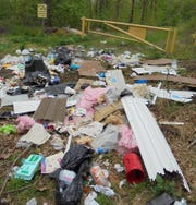 Trash is thrown out in a wooded area - right in front of a sign that warns against illegal dumping.