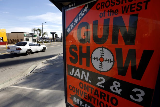 An advertisement for a gun show in Ontario is posted on a bus bench enclosure on E Street in San Bernardino on Monday, Dec. 7, 2015, just a few miles from the scene of a mass shooting that killed 14 people and injured 21 more. The sign is located in front of San Manuel Stadium, where a vigil was held for the victims. (Mark Boster/Los Angeles Times/TNS)