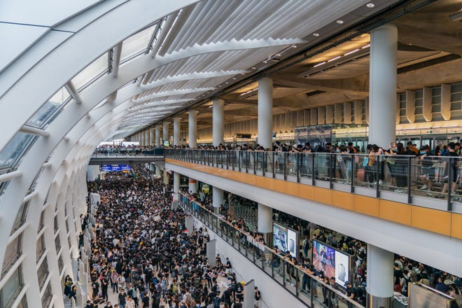 """HONG KONG, CHINA - AUGUST 12: Protesters occupy the Hong Kong International Airport during a demonstration on August 12, 2019 in Hong Kong, China. Pro-democracy protesters have continued rallies on the streets of Hong Kong against a controversial extradition bill since 9 June as the city plunged into crisis after waves of demonstrations and several violent clashes. Hong Kong's Chief Executive Carrie Lam apologized for introducing the bill and declared it """"dead"""", however protesters have continued to draw large crowds with demands for Lam's resignation and completely withdraw the bill. (Billy H.C. Kwok/Getty Images/TNS)"""