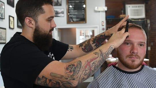 Cornerstoner Barbershop co-owner Jason McGarry (left) gives Nick Winand of Dallastown a straight razor shave.