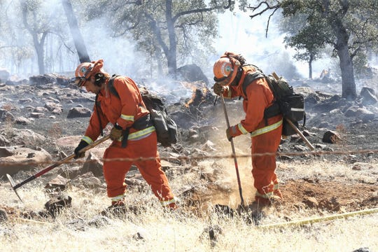 Inmates from the Trinity River Conservation Camp build a fire line off Dersch Road near Millville on Thursday afternoon, Aug. 15, 2019, at the Cottage Fires.