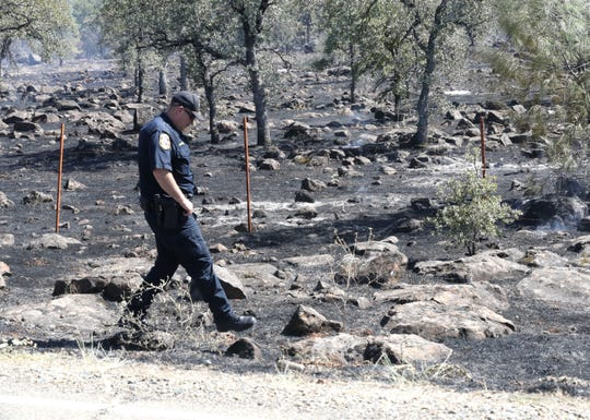 A California Department of Forestry and Fire Protection firefighter checks the side of Dersch Road near Millville where the Cottage Fires burned Thursday afternoon, Aug. 15, 2019.
