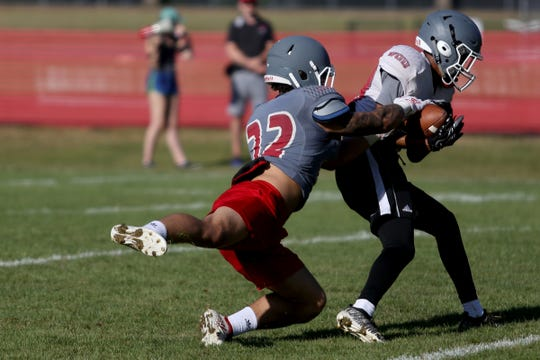 Isaiah Abraham (22) tries to tackle a teammate during a practice before the football season starts at Western Oregon University in Monmouth on Aug. 15, 2019.
