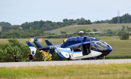 Emergency personnel walk away from a medical helicopter before it takes off from the scene of a car crash on Interstate 90 near the I-229 interchange on Thursday evening, August 15, in Sioux Falls.