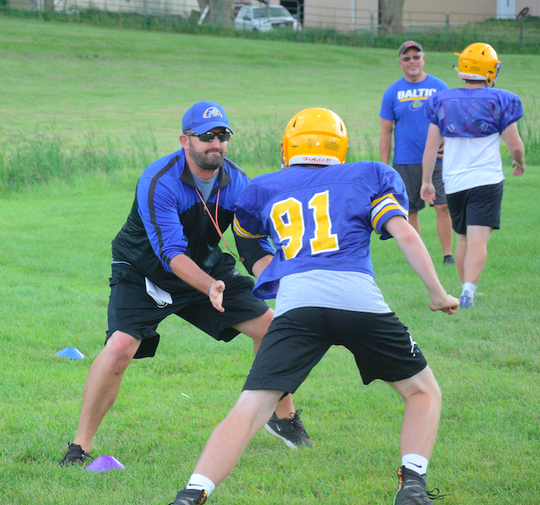 Baltic head coach Alan Baskerville goes through drills with player Andrew VanDam at a Baltic practice on Wednesday, August 14.