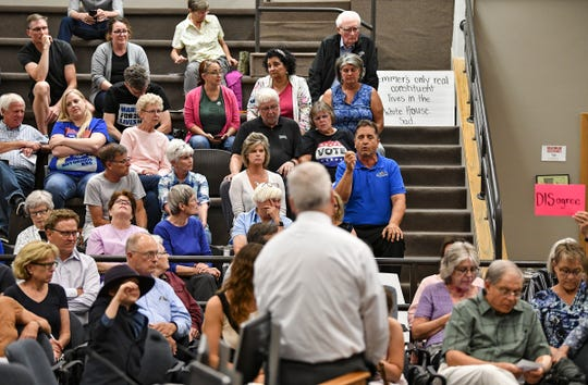 Audience members ask questions during a town hall meeting by U.S. Rep. Tom Emmer Wednesday, Aug. 14, 2019, at St. Cloud City Hall.