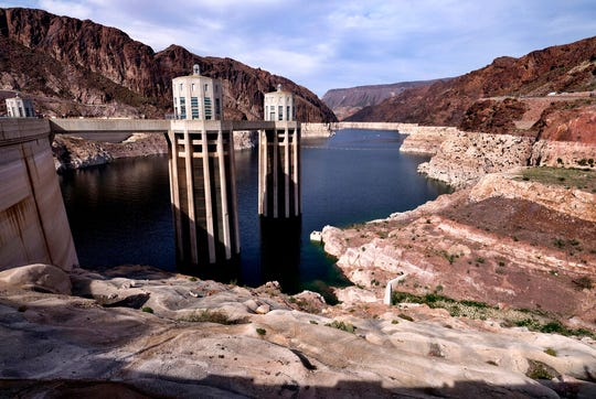 This March 26, 2019 photo shows the water level of the Colorado River, as seen from the Hoover Dam, Ariz. For the seven states that rely on the Colorado River that carries snowmelt from the Rocky Mountains to the Gulf of California, that means a future with increasingly less water for farms and cities although climate scientists say it's hard to predict how much less. The U.S. Bureau of Reclamation on Thursday, Aug. 15, 2019, will release its projections for next year's supply from Lake Mead, which feeds Nevada, Arizona and California. (AP Photo/Richard Vogel)