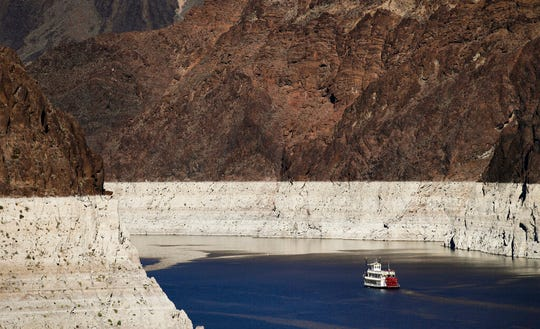 FILE - In this Oct. 14, 2015, file photo, a riverboat glides through Lake Mead on the Colorado River at Hoover Dam near Boulder City, Nev.  For the seven states that rely on the Colorado River that carries snowmelt from the Rocky Mountains to the Gulf of California, that means a future with increasingly less water for farms and cities although climate scientists say it's hard to predict how much less. The U.S. Bureau of Reclamation on Thursday, Aug. 15, 2019, will release its projections for next year's supply from Lake Mead, which feeds Nevada, Arizona and California. (AP Photo/Jae C. Hong, File)