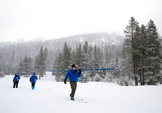 FILE - In this Feb. 28, 2019, file photo, John King, right, of the Department of Water Resources, carries the snowpack measuring tube as he crosses a meadow while conducting the third manual snow survey of the season at the Phillips Station near Echo Summit, Calif. A wet winter likely will fend off mandated water shortages for states in the U.S. West that rely on the Colorado River. But the snow and rain doesn't erase the impact of climate change in a region that's getting drier and hotter. U.S. officials will give a projection Thursday, Aug. 15 for the water supply from a key reservoir serving Arizona, California, Nevada and Mexico. (AP Photo/Rich Pedroncelli, File)