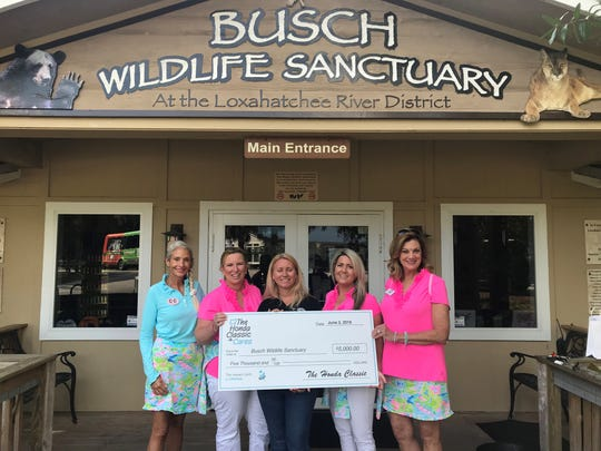 Amy Kight, center, executive director of Busch Wildlife Sanctuary, accepts a $5,000 donation from CouTOURe Club members Damiann Hendel, left, Deborah Jaffe, Ashley Schulties and Karen List. The CouTOURe Club is a volunteer organization of women dedicated to increasing awareness of The Honda Classic and its mission to raise money for children's charities.