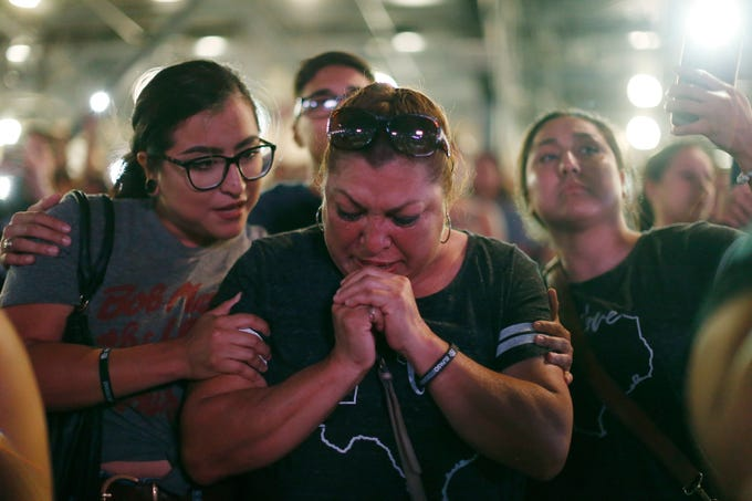 Maria Aguilar is comforted by her daughters Brenda, left, and Jessica, right, at the Community Memorial Service Wednesday, Aug. 14, at Southwest University Park. The memorial service was held for the 22 people that were killed in the shooting at Walmart Saturday, Aug. 3.