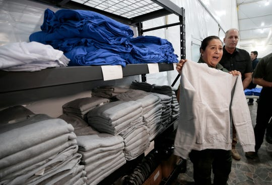 Interim El Paso Border Patrol Chief Gloria Chavez shows some of the clothing available to migrants as they arrive at the new soft-sided migrant holding facility in Tornillo, Texas, on August, 15. The new center is exclusively for adults; children will continue to be held at the Clint, Texas facility.