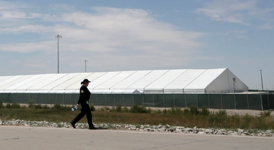 A guard walks between soft-sided tents at the new soft-sided migrant holding facility in Tornillo, Texas Thursday, August, 15, 2019. The new center is exclusively for adults; children will continue to be held at the Clint, Texas facility.