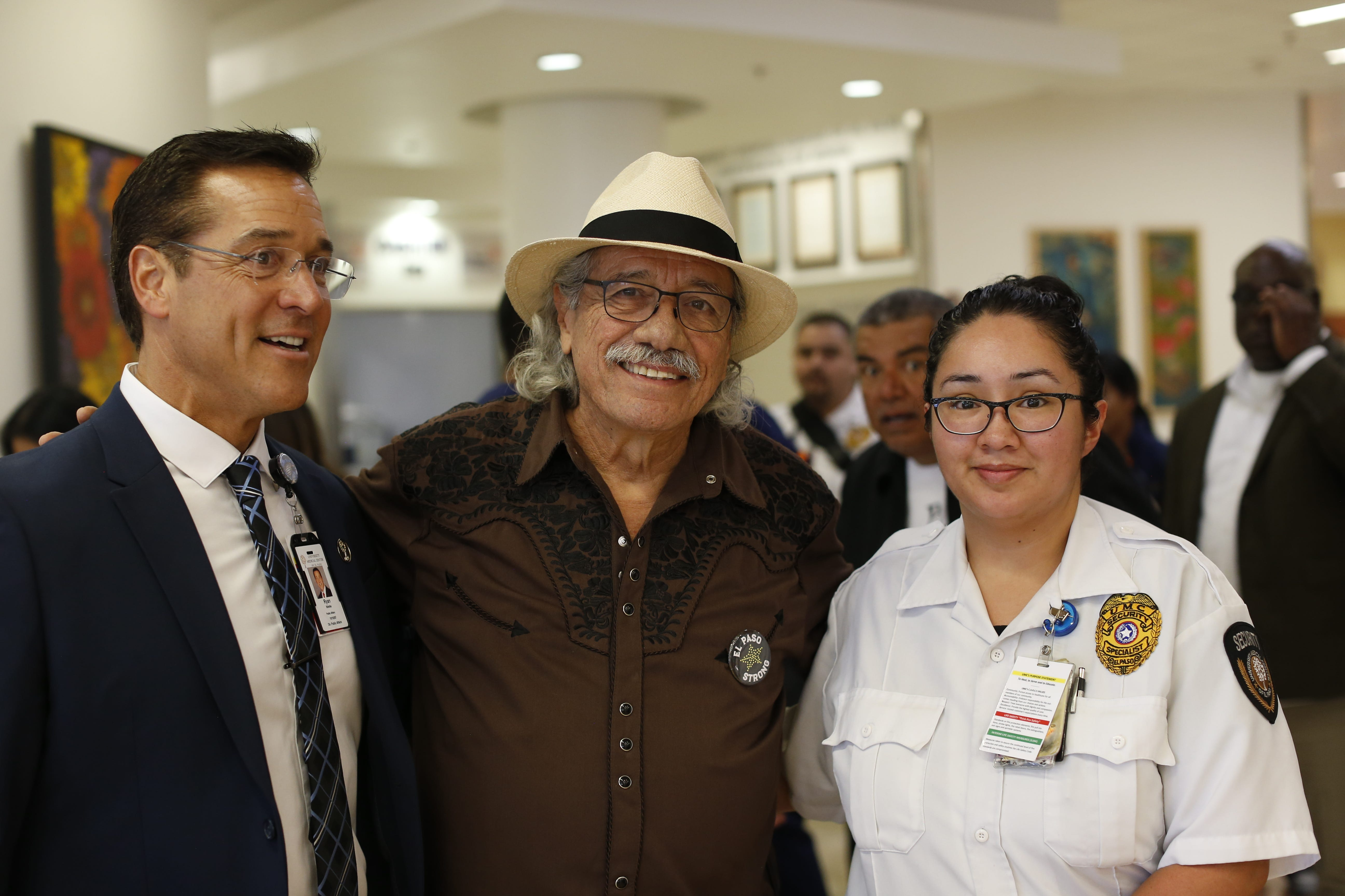 Edward James Olmos poses for a photo with University Medical Center staff with George Lopez popping out from the back.