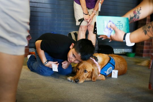 Bradley Palos, 9, leans down to sit next to comfort dog Joanna at the Community Memorial Service Wednesday, Aug. 14, at Southwest University Park. The dogs were brought to the park by Lutheran Church Charities.
