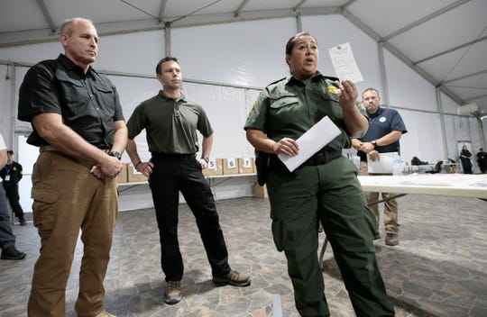 Interim El Paso Border Patrol Chief Gloria Chavez describes how migrants' belongings are tagged along side Acting Secretary of Homeland Security Kevin McAleenan, center, and Acting Commissioner of Customs and Border Protection Mark Morgan, left, at the new soft-sided migrant holding facility in Tornillo, Texas Thursday, August, 15, 2019.