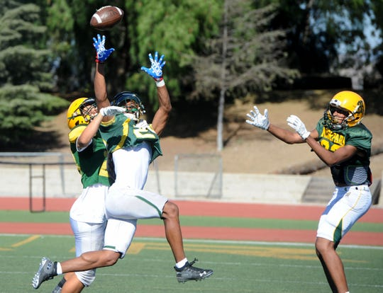 Michael Holland, center, stretches while attempting to catch a pass between two teammates at a Moorpark High practice.