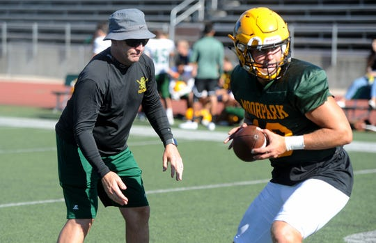 Head coach Ryan Huisenga works with quarterback Blake Sturgill during a Moorpark High practice.