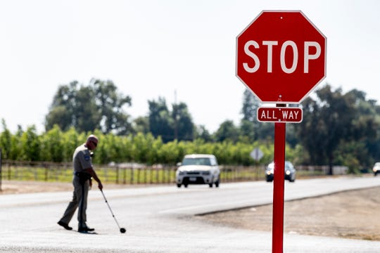 CHP officer J. Morgan takes additional measurements at the intersection of Avenue 256 and Road 124 on Wednesday, August 14, 2019. The intersection was changed from two-way stop to four-way stop in June of this year. There have been two collisions, including one that killed a 10-year-old last week, since the change. There are other intersections in the area with similar changes.