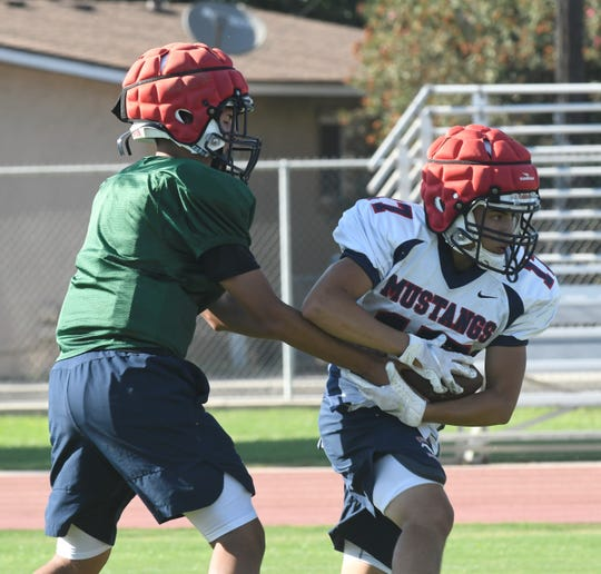 Tulare Western quarterback Elijah Burrell, left, hands the ball off during practice on Aug. 12, 2019 in Tulare.