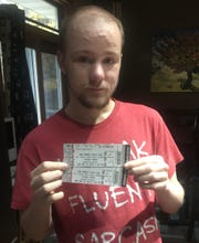 Kameron Frisinger displays a couple of tickets to a professional wrestling event.