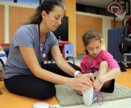 Therapist Tara Sullivan helps Ora Goldgrab, 6, tie her shoe during a program that help kids with hemispheric mobility issues to use their weak side at Blythedale Children's Center in Valhalla Aug.14, 2019.  Goldgrab suffered a stroke in utero.