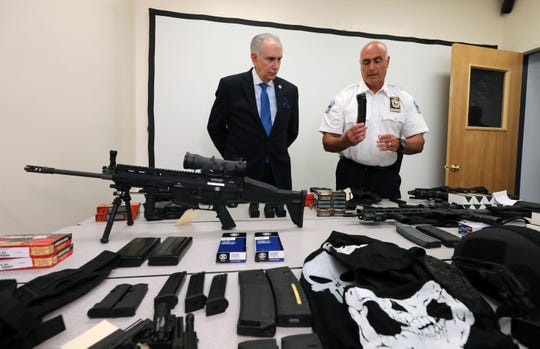 Westchester County District Attorney Anthony A. Scarpino Jr., and Tuckahoe Police Chief John Costanzo, look over a table full of weapons and other material, after the arrest of a 47-year old male for multiple criminal possessions of weapons charges, during a press conference Aug. 14, 2019.