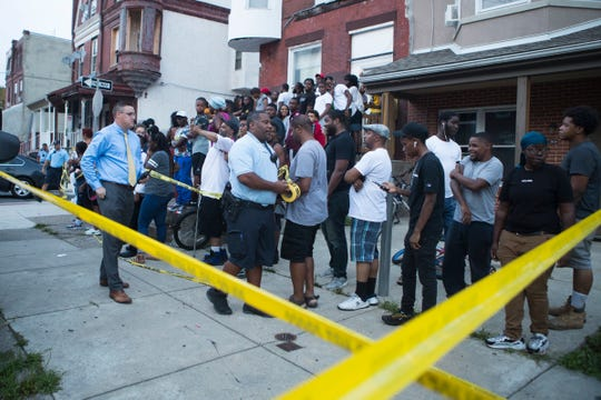A crowd waits for developments during a police standoff with the suspected shooter of six Philadelphia Police Officers Wednesday afternoon on North 15th Street in Philadelphia, Pa. The suspect was apprehended early Thursday morning after a long standoff with police on North 15th Street.