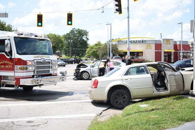 A first responder checks on the man inside the silver Honda Accord following a crash on Maple Avenue Thursday afternoon.