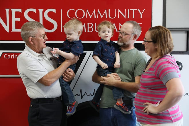 Bernie Hiles holds 2-year-old Jack Lindamood while visiting with his father Daryl Lindamood, mother Linda Wheeler and brother Marvin. Hiles was honored by Genesis Community Ambulance on Thursday after rescuing the boys from the middle of Frazeysburg Road in Nashport last week.