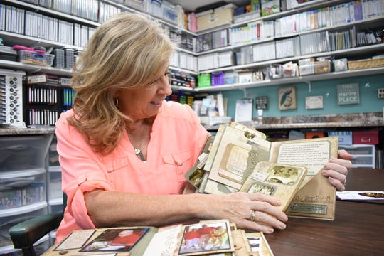 Christy Applegate, owner of Christy's Main Street Memories, flips through a scrapbook she made for her father less than two years before he died.