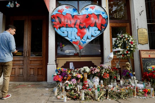 In this Aug. 7, 2019 file photo, a pedestrian passes a makeshift memorial for the slain and injured victims of a mass shooting that occurred in the Oregon District early Sunday morning in Dayton, Ohio.