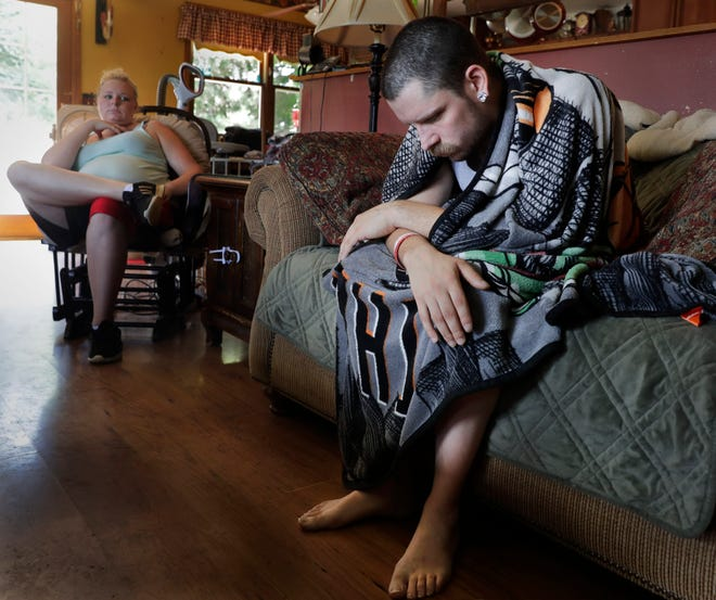 In this Monday, July 29, 2019 photo, Dylan Nelson, of Burlington, Wis., and his sister, Andrea, sit for an interview. He was rushed to the hospital in June by his sister last month with severe breathing problems. Doctors believe he and about two dozen other young adults suffered serious lung injuries after vaping nicotine or THC, or both.