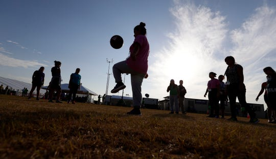 In this July 9, 2019, file photo, immigrants play soccer at the U.S. government's newest holding center for migrant children in Carrizo Springs, Texas.