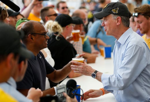 Former Colorado Gov. John Hickenlooper and 2020 presidential candidate, serves a beer to Atanu Chakravarty at Iowa State Fair on Aug. 10, 2019.