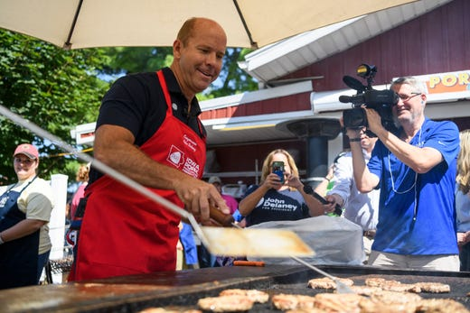 John Delaney, a former Maryland representative and 2020 presidential candidate, grills burgers at the Iowa Pork Producers tent during the second day of the Iowa State Fair on August 9, 2019.
