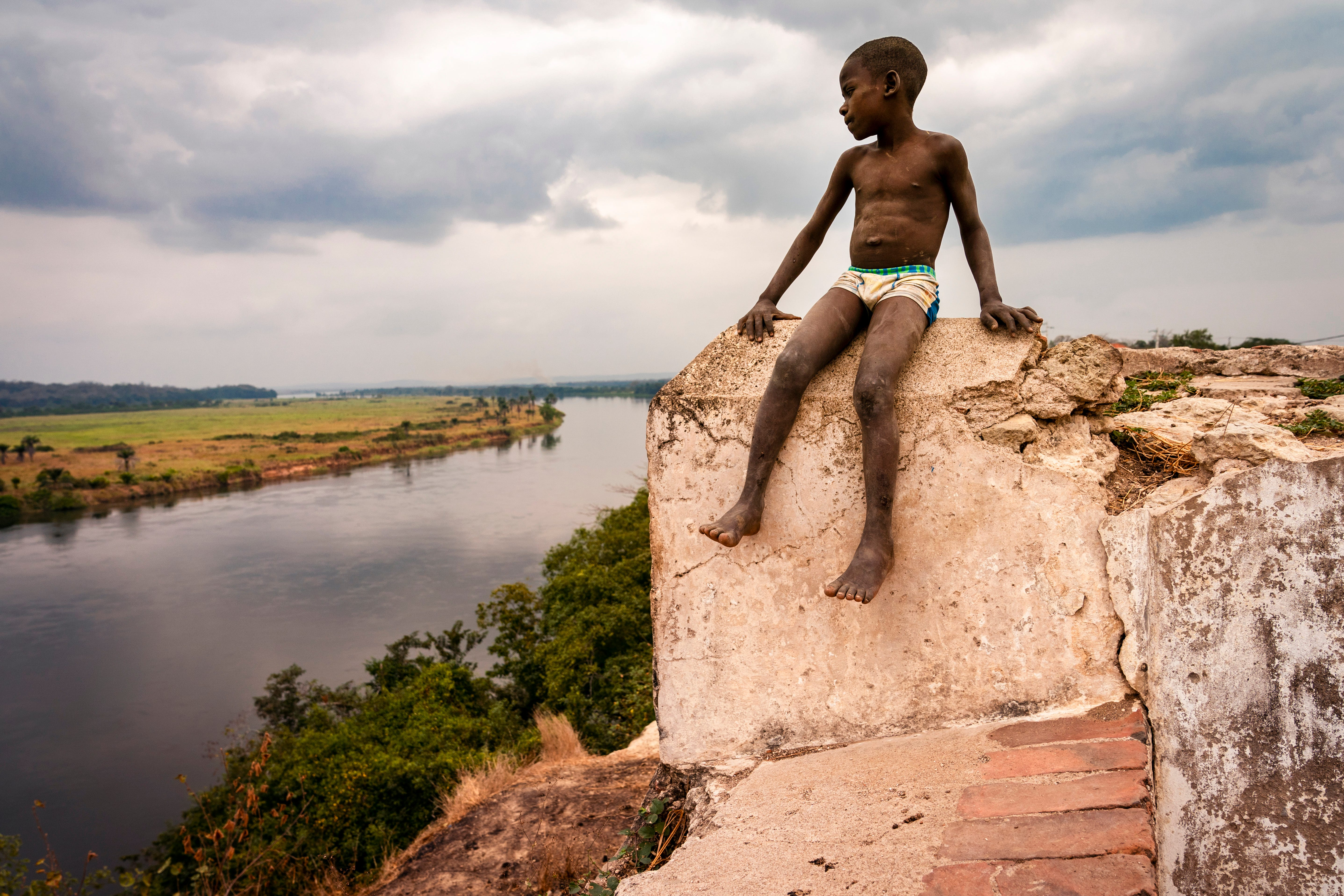 A boy looks out toward the Kwanza river from the Fortaleza de Massangano in Angola. The fort was a base of operations for the Portuguese. Captured Africans were branded and baptized before being taken to the coast and loaded onto slave ships.