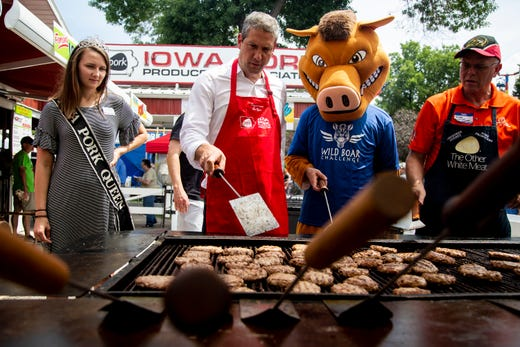 Rep. Tim Ryan, D-Ohio, takes a turn at the grill, flipping pork burgers for the Iowa Pork Producers during the Iowa State Fair on Aug. 10, 2019.