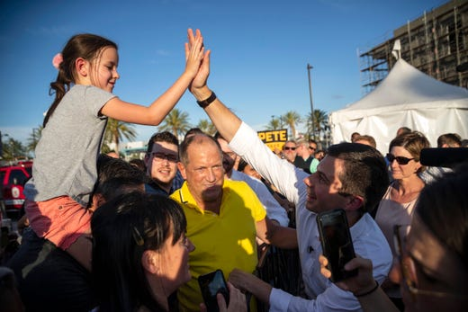 Democratic presidential candidate Pete Buttigieg high-fives a young supporter during a rally in Las Vegas, NV, on August 2, 2019.