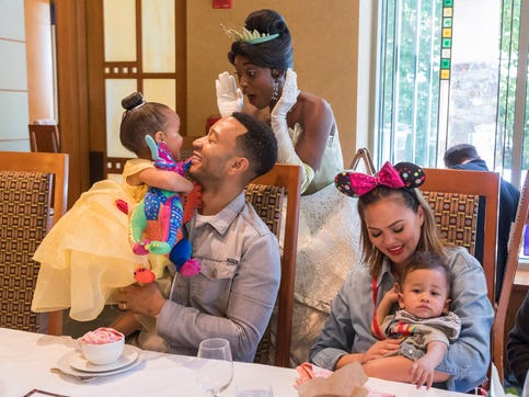 ANAHEIM, CALIFORNIA - APRIL 12: In this handout image, John Legend, Chrissy Teigen, their daughter Luna and son Miles share a moment with Princess Tiana during the Disney Princess Breakfast Adventures at Disney's Grand Californian Hotel on April 12, 2019 in Anaheim, California. (Photo by Joshua Sudock/Disneyland Resort via Getty Images) ORG XMIT: 775328167 ORIG FILE ID: 1136588468