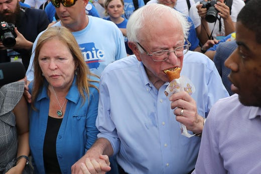 Democratic presidential candidate Sen. Bernie Sanders, I-VT, munches on a corn dog as he and his wife Jane O'Meara Sanders walk around the Iowa State Fair on August 11, 2019.