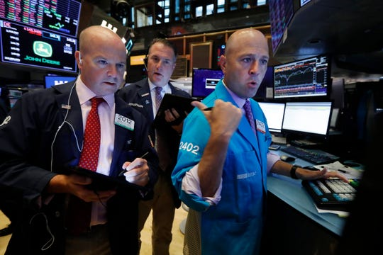 Traders Patrick Casey, left, and Jonathan Corpina, center, work with specialist Jay Woods on the floor of the New York Stock Exchange, Wednesday, Aug. 14, 2019.