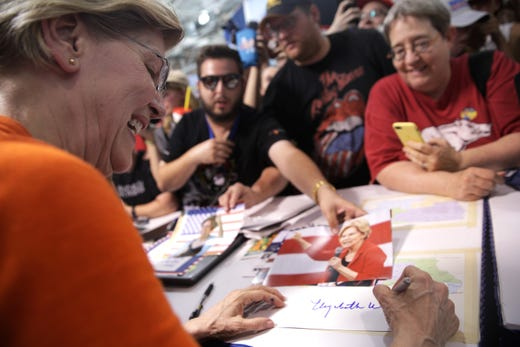 Democratic presidential candidate U.S. Sen. Elizabeth Warren, D-MA, signs autographs for visitors at the Iowa Democratic Party booth after she delivered a campaign speech on August 10, 2019 in Des Moines, Iowa.