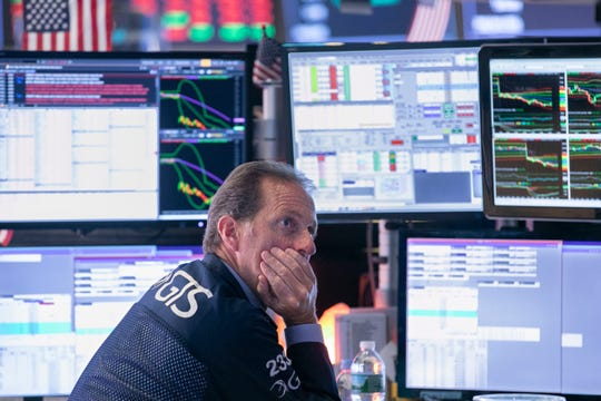 Specialist Glenn Carrel works at his post on the floor of the New York Stock Exchange, Wednesday, Aug. 14, 2019.
