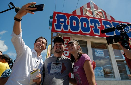Democratic presidential candidate South Bend Mayor Pete Buttigieg takes a selfie with visitors Tuesday, Aug. 13, 2019, at the Iowa State Fair in Des Moines, Iowa.