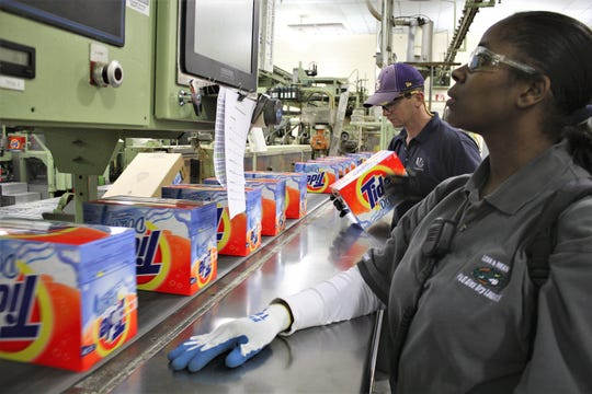 Employees at Procter & Gamble's plant in Pineville check boxes of Tide as they move on a conveyor belt towards the shipping area.