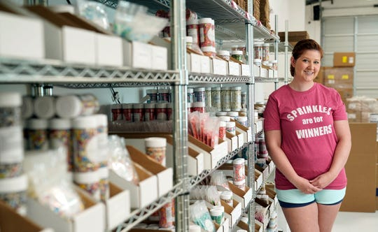 Elizabeth Butts, owner of Sprinkle Pop, a company based in Houston that makes upscale sprinkles for bakers, poses inside her business in Houston. Butts is building out and equipping a 10,000 foot facility for storage and shipping. She's reinvesting the company's profits rather than seeking investors, which will make it easier for her to run the company, but she also doesn't want to burden her company with debt.