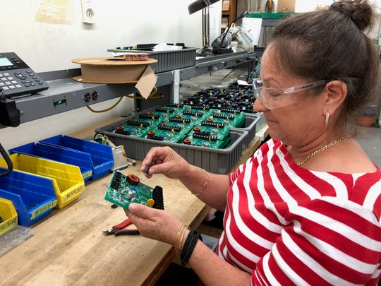 Alejandrina Valdez puts together a circuit board at Micro-Air Inc. in Allentown.