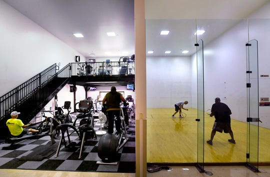 Racquetball players ready themselves for another game while others ride exercise machines in a converted court at the Redbud YMCA on Friday.